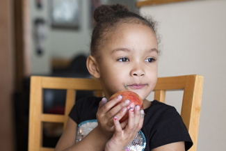 Small girl eating apple and looking away
